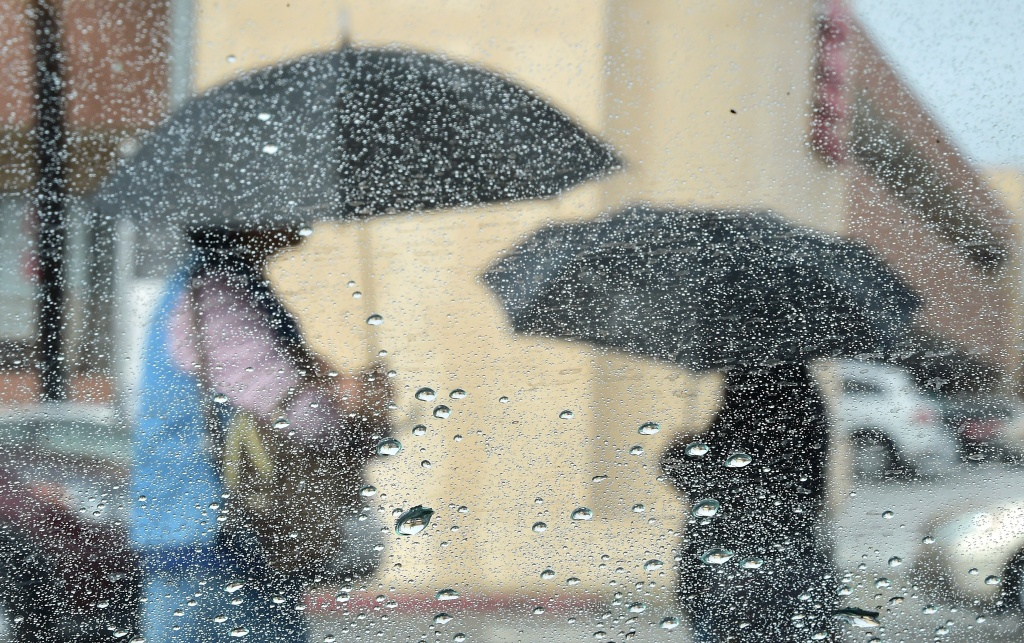 In Los Angeles, women use umbrellas under a steady September 2015 rainfall. A series of storms related to El Niño is expected to dump up to six inches of rain on the Southland this week.