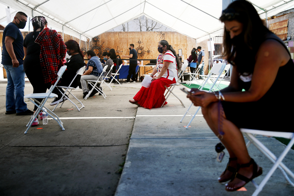 Volunteer Miriam Lopez Ambrosio (C), a folkloric dancer from Oaxaca, waits to assist people with their vaccination appointments at a clinic targeting Central American Indigenous residents at CIELO, an Indigenous rights organization, on April 10, 2021 in Los Angeles, California.