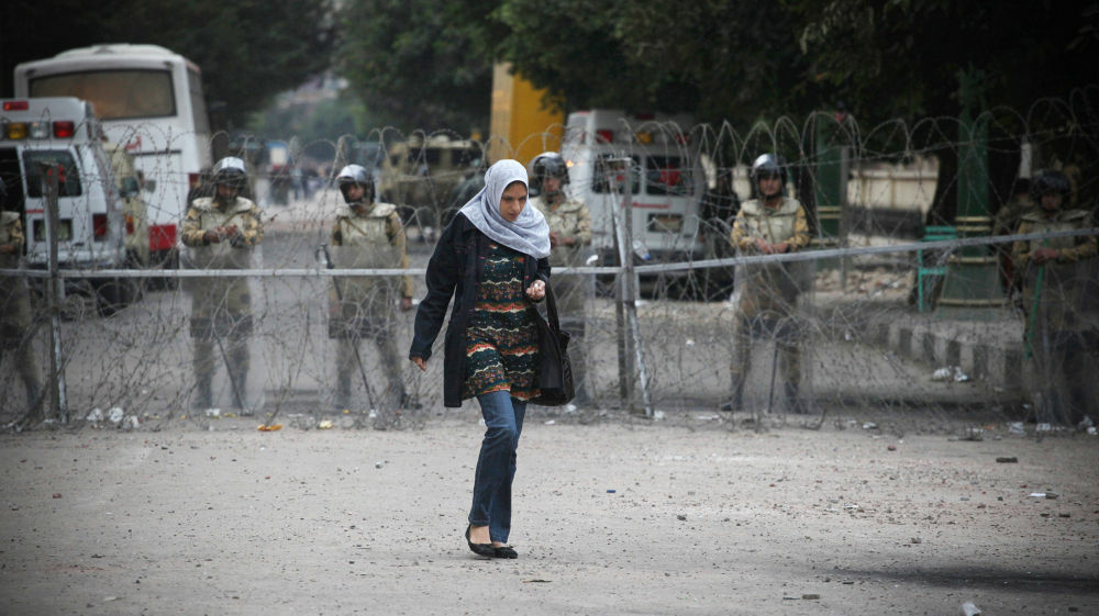 A woman walks past Egyptian military near Tahrir Square in Cairo, Egypt, on Sunday. Protesters have clashed with security forces in the days leading up to Monday's parliamentary elections, and women are being targeted.