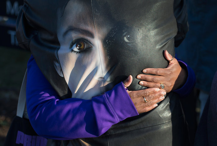 Fans comfort each other while visiting a memorial outside Paisley Park, the home and studio of Prince, on April 22, 2016.