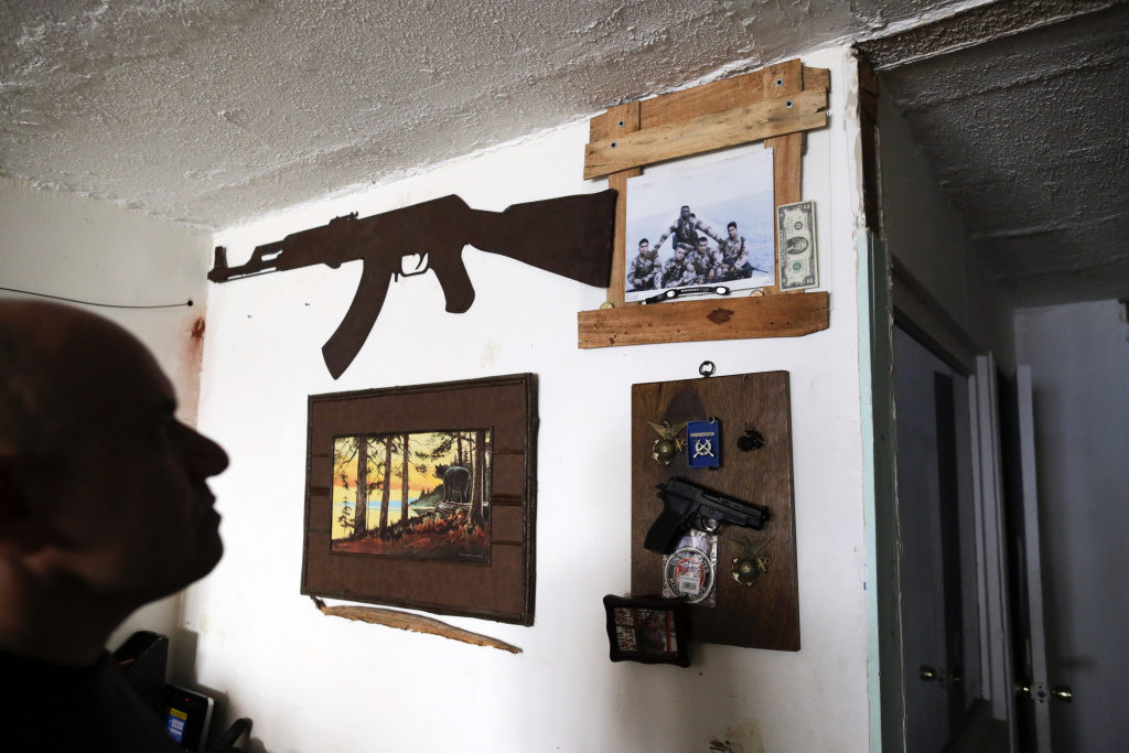 U.S. Marine veteran Antonio Romo — on Feb. 13, 2017 — looks at a replica of a pistol and other military items from his time in the service, mounted on his apartment wall in Tijuana, Mexico. Romo, who says he turned to alcohol and narcotics to try to quiet his nightmares and made multiple suicide attempts, fell into dealing and was arrested for selling cocaine. After getting out of prison in 2008, Romo was deported to Mexico, from where he had migrated without permission at age 12.