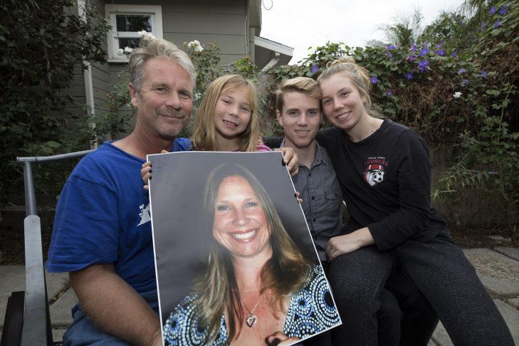 Husband Bob Patterson, left, and his children Brooke, Robert and Amber. They hold a photograph of Lisa Patterson in Lomita, California, on Oct. 30, 2017. Lisa Patterson was killed in the Oct. 1 shooting attack in Las Vegas.