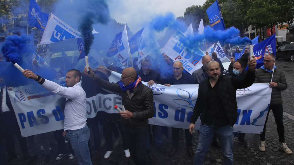 French police unionists fire blue flares as they demonstrate with a banner reading