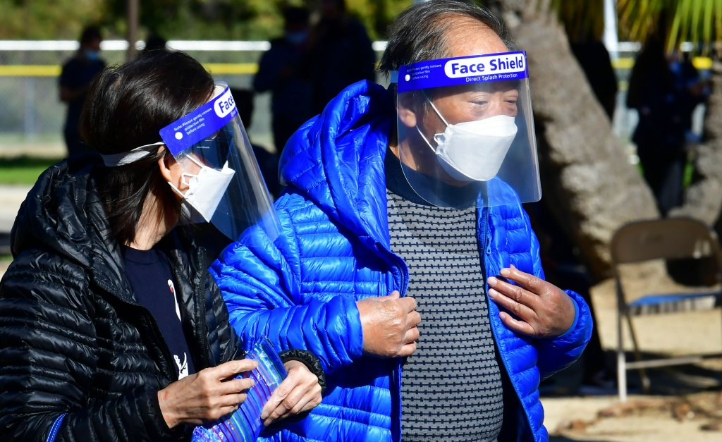 Elderly Asian Americans wear face shields and masks at a Covid-19 vaccination site in Los Angeles, California on February 23, 2021. - City-wide vaccination sites reopened after a temporary shutdown due to inclement weather which affected transportation of the vaccine. A California program meant to improve availability of Covid-19 vaccines in underserved minority communities is reportedly being misused by people in wealthier areas of Los Angeles, grabbing  appointments reserved for residents of Black and Latino neighborhoods, according to a Los Angeles Times report on February 22. (Photo by Frederic J. BROWN / AFP) (Photo by FREDERIC J. BROWN/AFP via Getty Images)