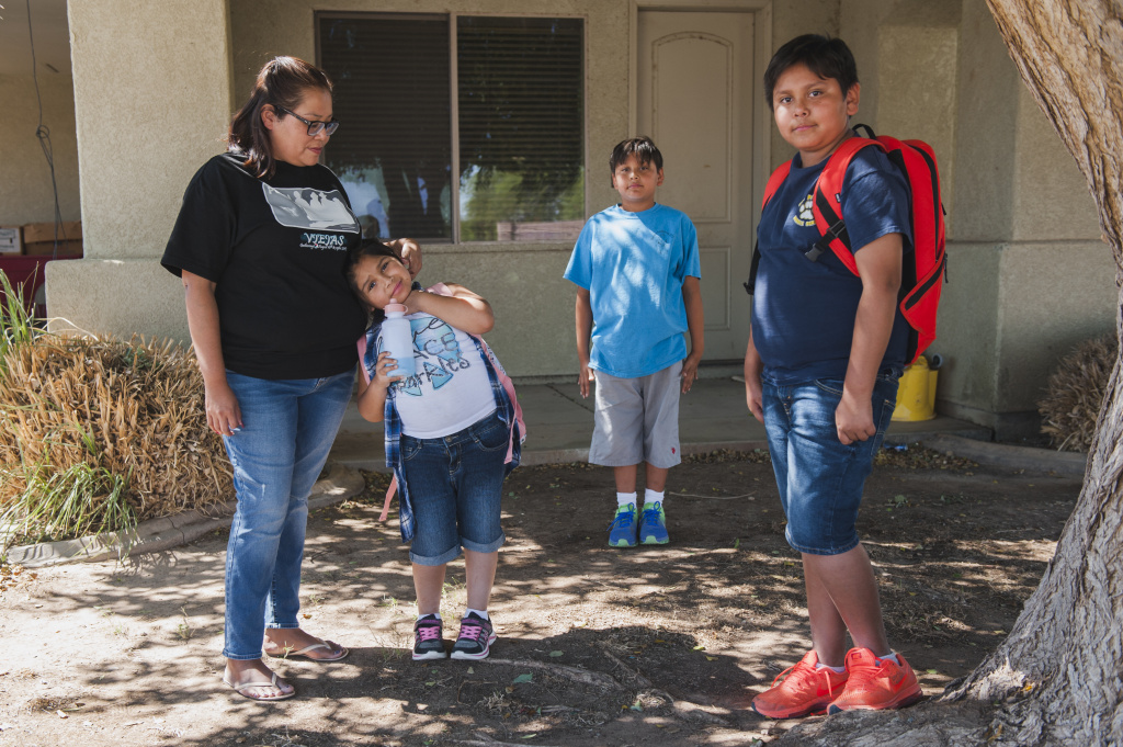 Celisse Cornejo stands with her children Rubi, Alfred, and Jasper outside the two bedroom home where they live along with Cornejo's husband and a nephew on the Fort Yuma Indian Reservation. The Quechan Tribe is using a new tax credit program to fund construction of a 44-unit affordable housing project.