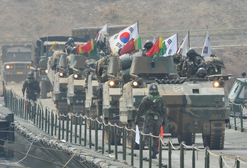 South Korean K-200 armored vehicles move over a temporary bridge during a river-crossing military drill in Hwacheon near the border with North Korea on April 1, 2013. South Korea's new president promised a strong military response to any North Korean provocation after Pyongyang announced that the two countries were now in a state of war.