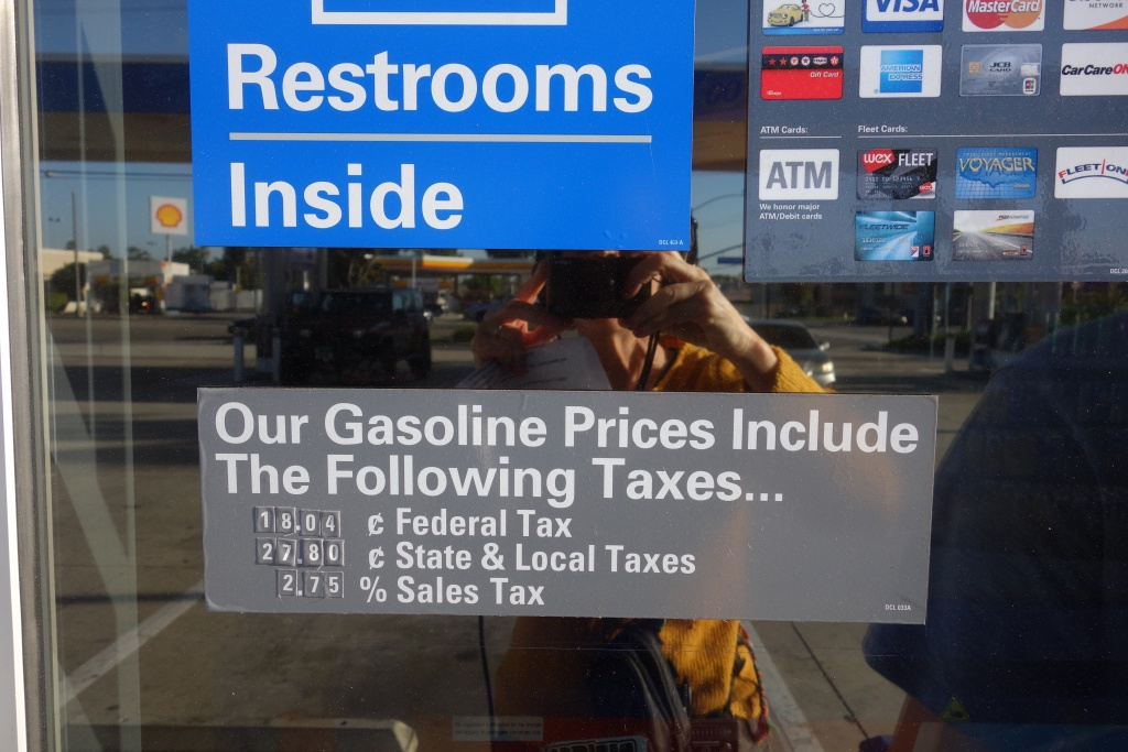 California gas stations post signs showing that each gallon of gas carries a federal 18-cent tax and a 27.8-cent state tax. Sales taxes are also charged on gas purchases.