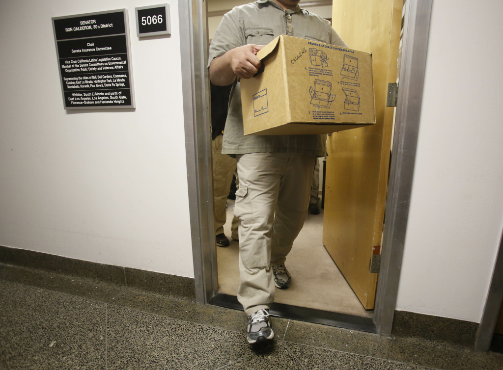 An FBI agent carries out a box as he leaves the Capitol office of State Sen. Ron Calderon, D-Montebello, in Sacramento, Calif., Tuesday, June 4, 2013.