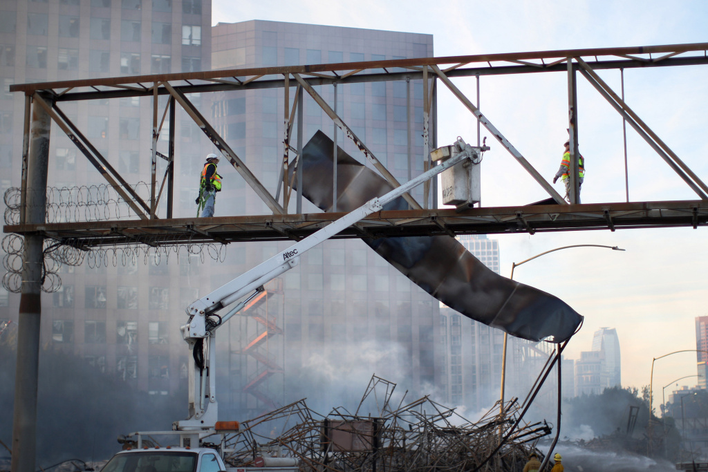 Workers toss a sign over the 110 freeway that was ruined in an early morning fire that destroyed a seven-story apartment building under construction on December 8, 2014 in Los Angeles, California.