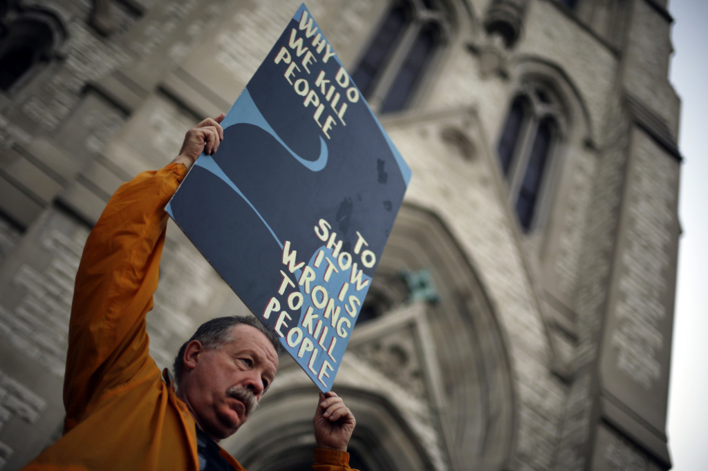 Death penalty opponent Herve Deschamps holds a sign during a vigil outside St. Francis Xavier College Church in St. Louis, hours before 2014 scheduled execution of death row inmate Russell Bucklew.