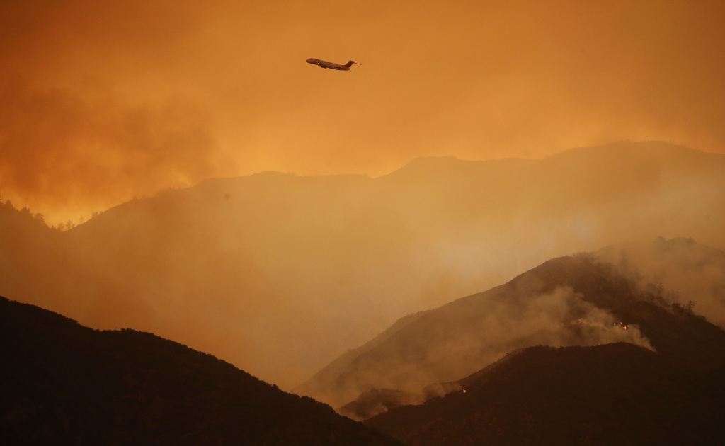 A firefighting airplane flies above the Holy Fire as it burns in Cleveland National Forest on August 8, 2018 in Corona, California. The fire has burned at least 6,200 acres and destroyed twelve structures.
