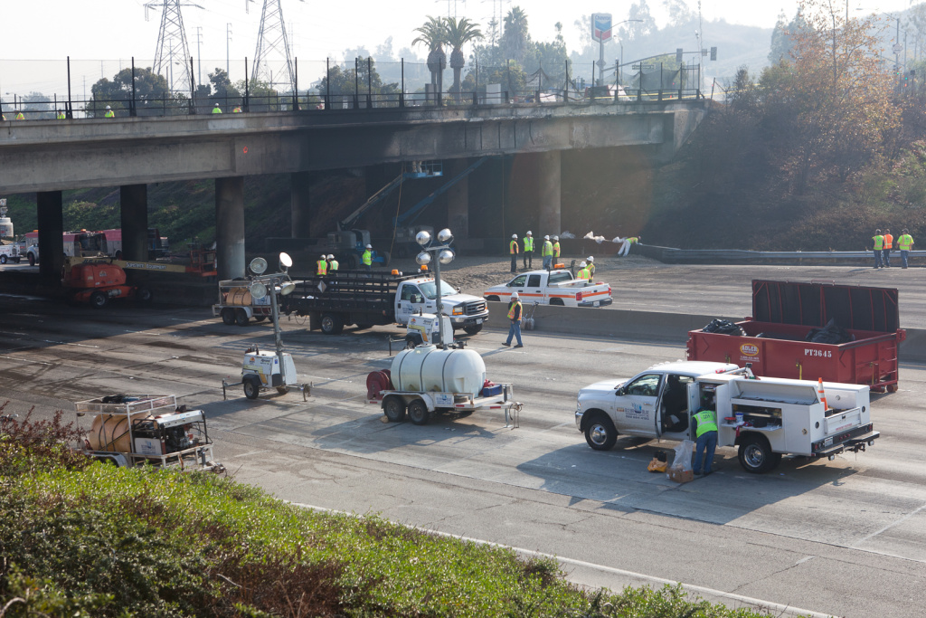 Workers are preparing to demolish the bridge over the 60 Freeway by laying down sand and inspecting the structure of the bridge.