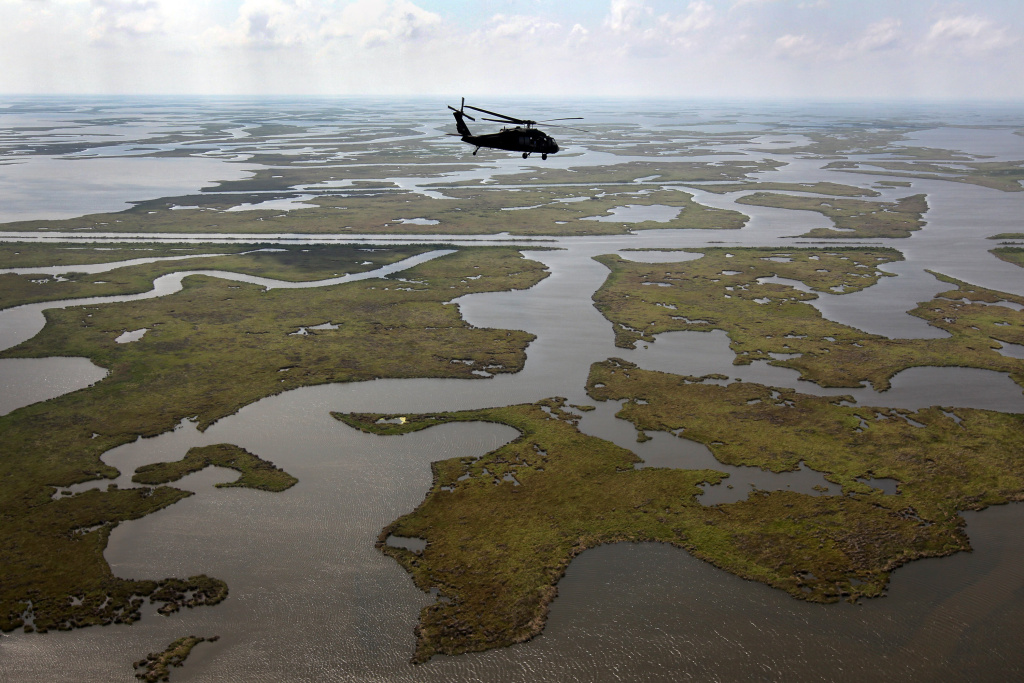 A Louisiana National Guard black hawk helicopter flies over marshland on April 19, 2011, in route to Middle Ground in southern Louisiana. A year after the BP oil spill coated Gulf coast marshes and beaches, BP claims that most of the oil has been removed. Louisiana Wildlife and Fisheries says, however, that much of the cleaning has been superficial, as the oil has seeped into the soil, killing marshes and further eroding the state's damaged delta ecosystem.