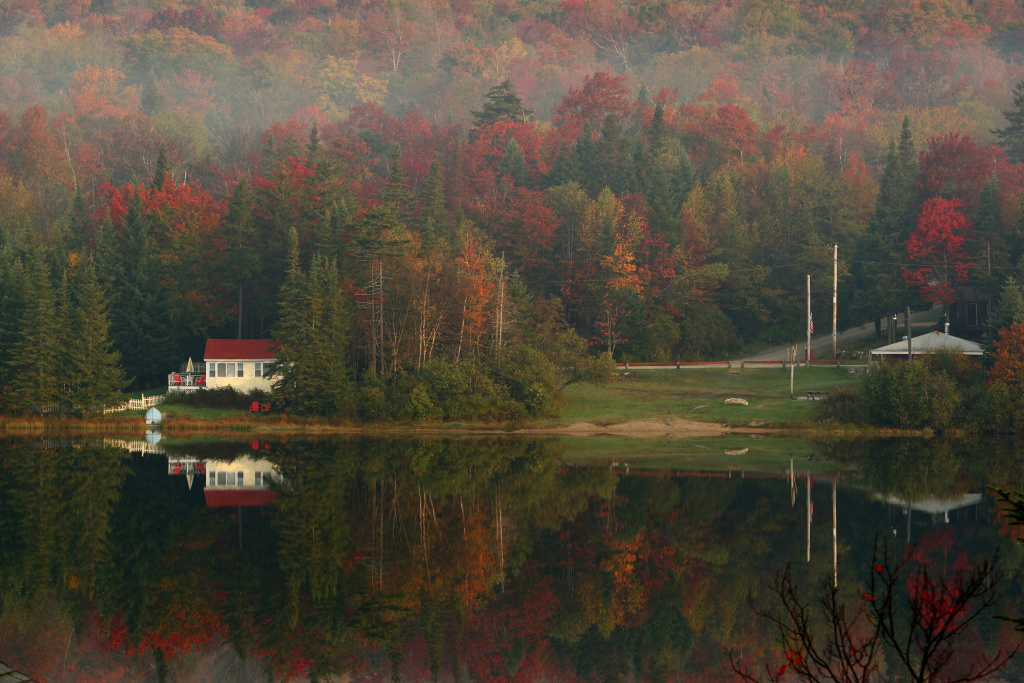 Leaves begin turning color in the early morning mist on October 6, 2007 as houses and trees are reflected on Big Pond near Woodford, Vermont.