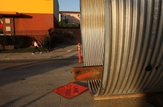 A pedestrian passes a city sewer project February 18, 2009 in Los Angeles, California.