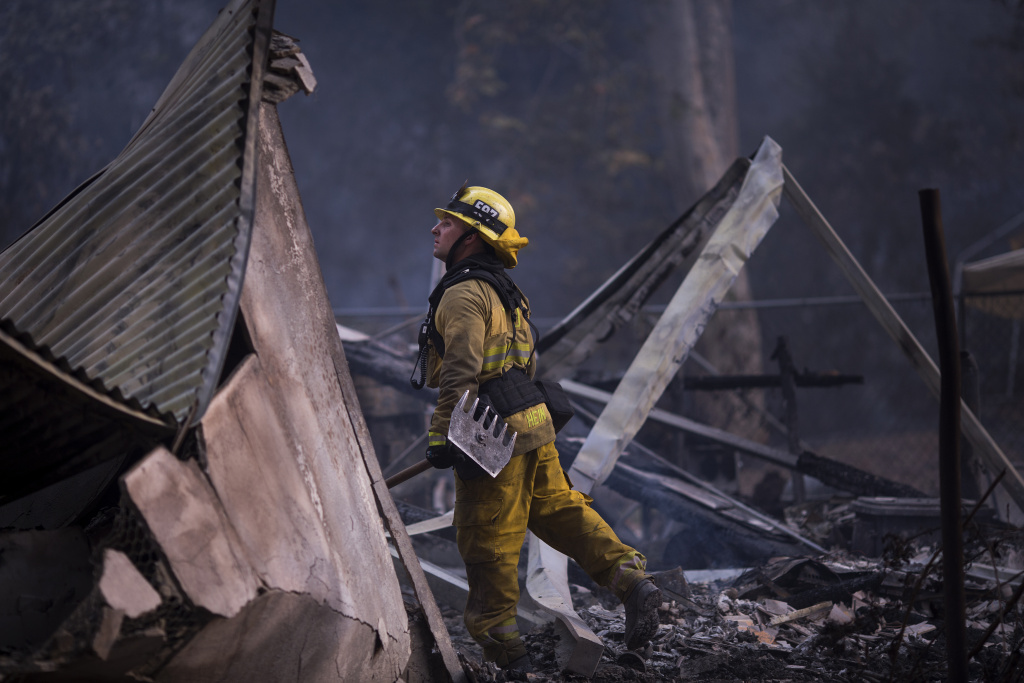 A firefighter looks through the smoldering ruins of a burned house near Casitas Pass Road as the Thomas Fire continues to grow on December 10, 2017 near Carpinteria, California.