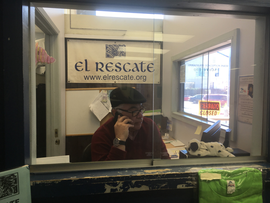 Salvador Sanabria, executive director of El Rescate, works the intake window one recent Saturday as Central Americans with temporary protection from deportation lined up outside the door for legal screenings. The Trump administration has announced it is ending the protection for Salvadoran and Nicaraguan immigrants; Hondurans will learn their fate soon.