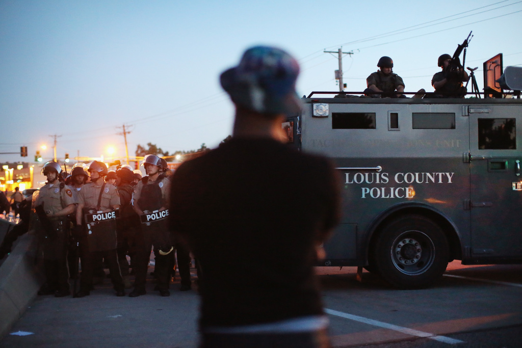 Police stand watch as demonstrators protest the shooting death of teenager Michael Brown on August 13, 2014 in Ferguson, Missouri. Brown was shot and killed by a Ferguson police officer on Saturday. Ferguson, a St. Louis suburb, is experiencing its fourth day of violent protests since the killing.