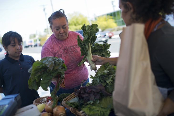 Mary Muñoz, right, and her daughter, Melanie Muñoz, shop for fresh produce at Community Services Unlimited's Village Market Place produce stand in South Los Angeles on Friday, April 10, 2015. The produce stand is in the parking lot of Century Market every Friday from 2 to 5 p.m.