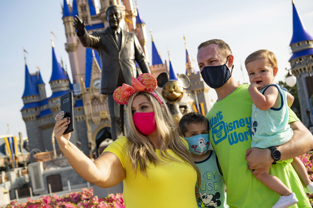In this handout photo provided by Walt Disney World Resort, guests stop to take a selfie at Magic Kingdom Park at Walt Disney World Resort on July 11, 2020 in Lake Buena Vista, Florida.