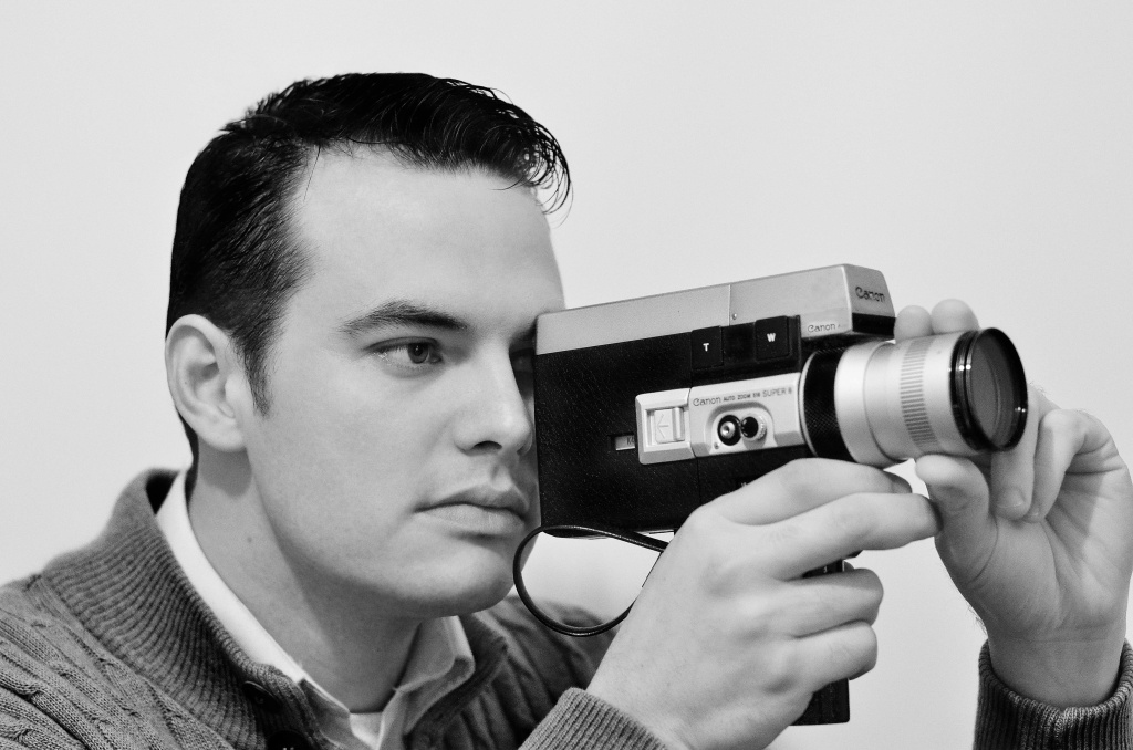 A man uses a Super 8 camera.