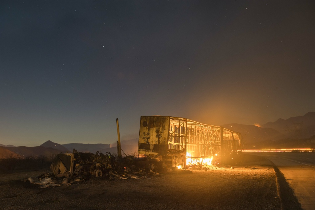 The Blue Cut Fire and a burned out semi truck seen off Interstate 15 in the Cajon Pass Tuesday evening.     The Blue Cut Fire burns in San Bernardino County Tuesday evening August 16th, 2016. The fire had burned 15,000 acres and was 0% contained, with multiple structures threatened and destroyed. Interstate 15 was also shut down at the 215.