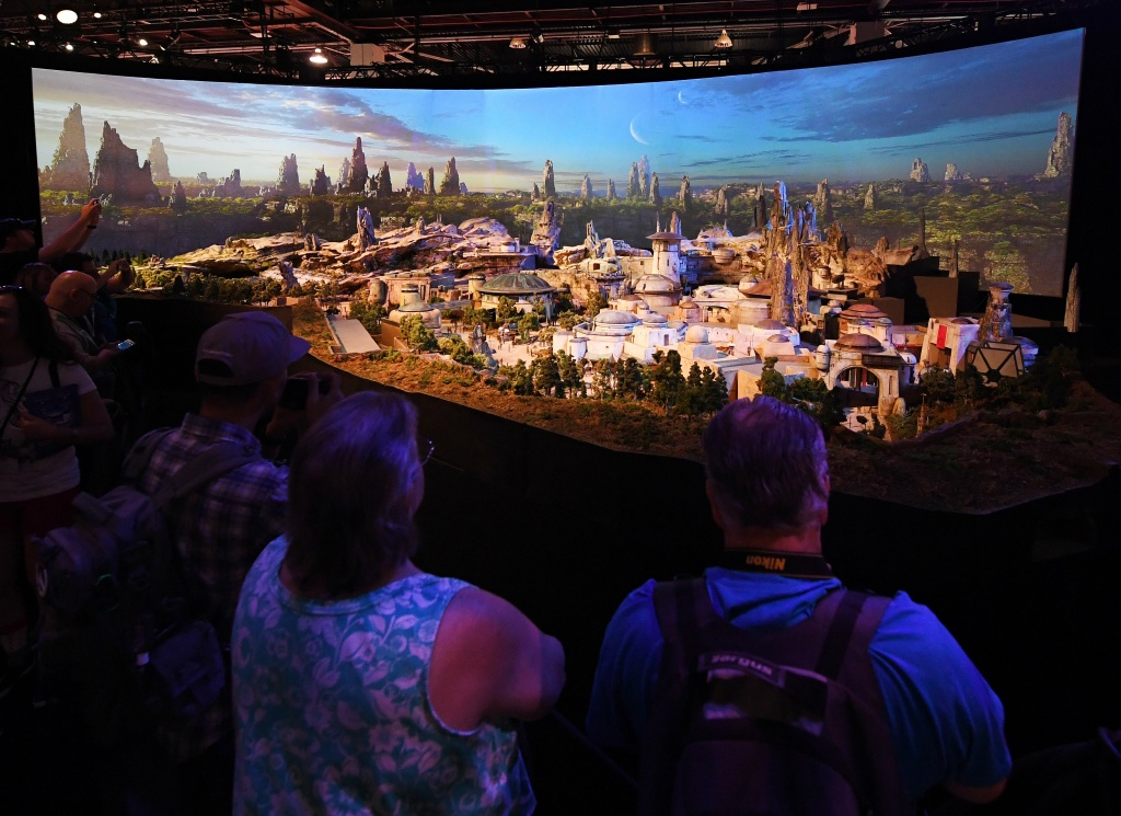 Fans view a model of the new Star Wars theme park that will open in the California and Florida Disneyland Parks in 2019 during the D23 expo fan convention at the Convention Center in Anaheim, California, on July 15, 2017.