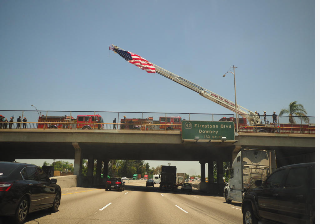 Long Beach firefighters wait on overpasses to the 710 Freeway to pay their respects to the procession carrying the body of slain firefighter Dave Rosa.