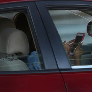 A driver uses a phone while behind the wheel of a car on April 30, 2016 in New York City.