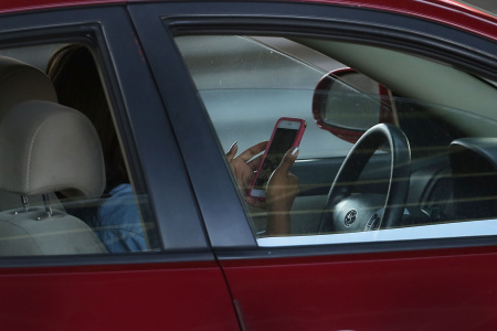 A driver uses a phone while behind the wheel of a car on April 30, 2016 in New York City
