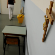 A crucifix hangs on a wall as a teacher