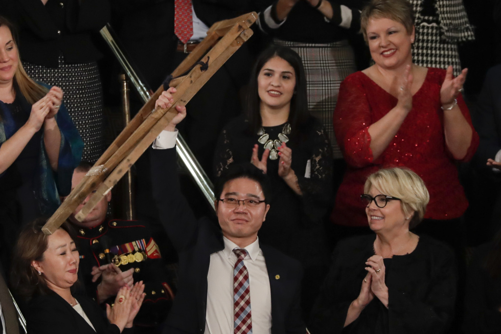 Ji Seong-ho holds up his crutches after his introduction by President Trump during the State of the Union address on Tuesday.
