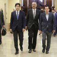 Former U.S. Attorney General Eric Holder, center, flanked by California Senate President Pro Tem Kevin de Leon, D-Los Angeles, left, and Assembly Speaker Anthony Rendon, D-Paramount, walks to a meeting with Calif., Gov. Jerry Brown, Tuesday, Feb. 7, 2017, in Sacramento, Calif.