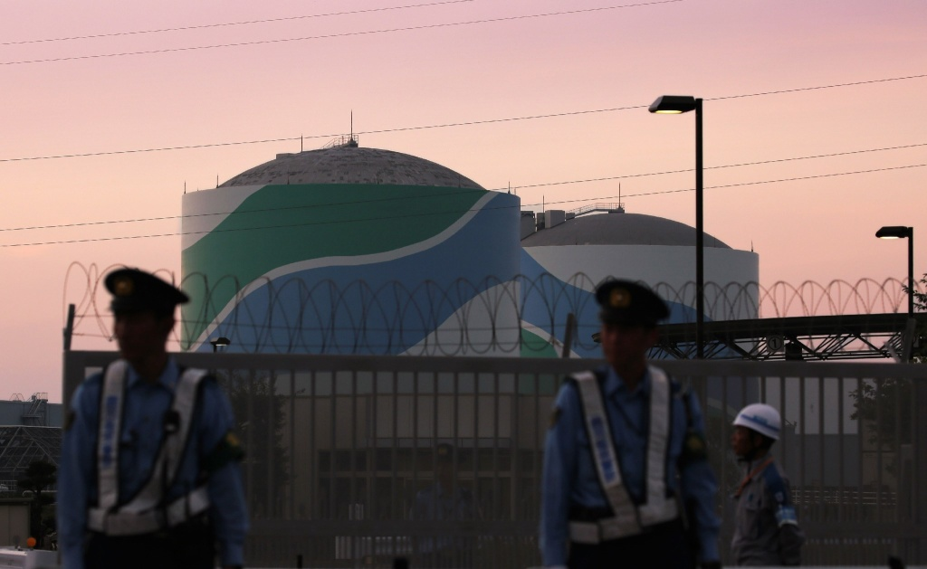 Nuclear reactor buildings of the Kyushu Electric Power Sendai nuclear power plant are seen behind police officers standing guard in the twilight in Satsumasendai in Kagoshima prefecture, on Japan's southern island of Kyushu on August 11, 2015. Japan on August 11 switched on a nuclear reactor, officials said, ending a two-year shutdown in the energy-hungry country that was sparked by public fears following the 2011 Fukushima crisis, the worst atomic disaster in a generation.