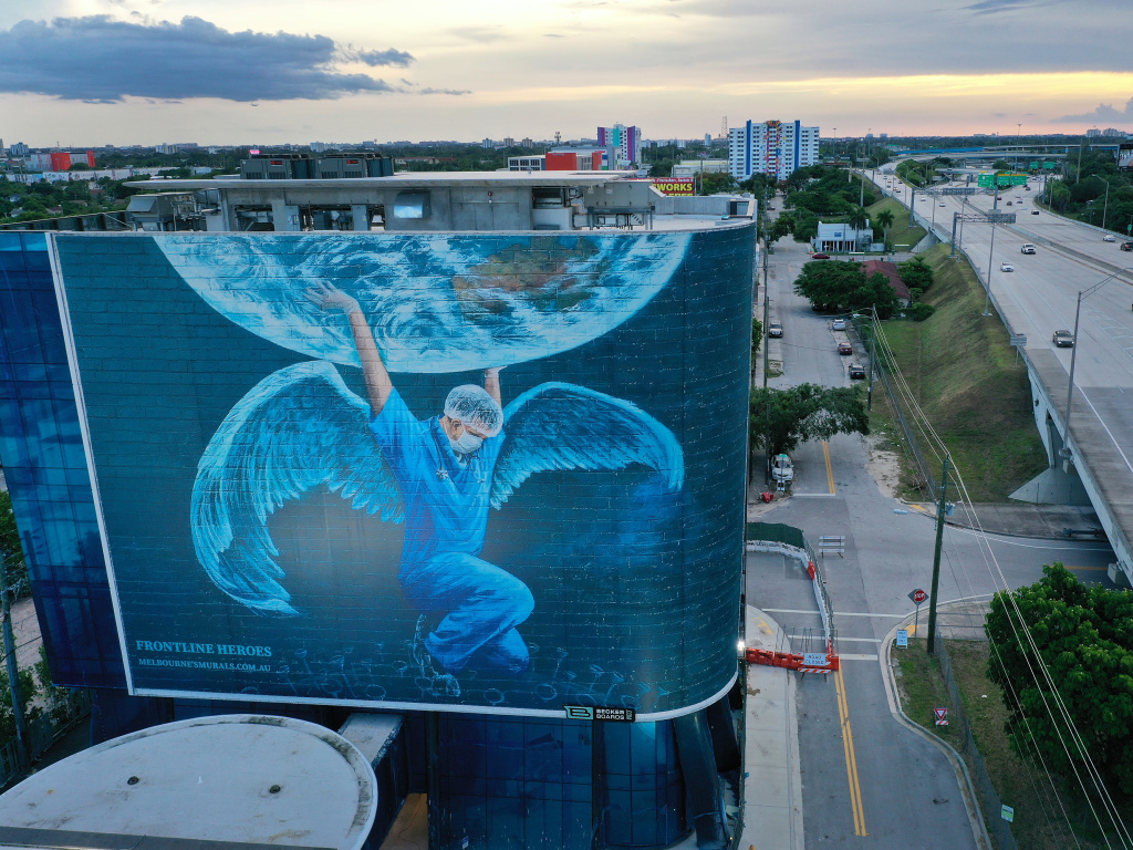 A billboard in Miami — where coronavirus cases continue to surge — depicts a medical worker holding up the world. The number of coronavirus deaths worldwide has surpassed 600,000, with more than 140,000 of those in the U.S.