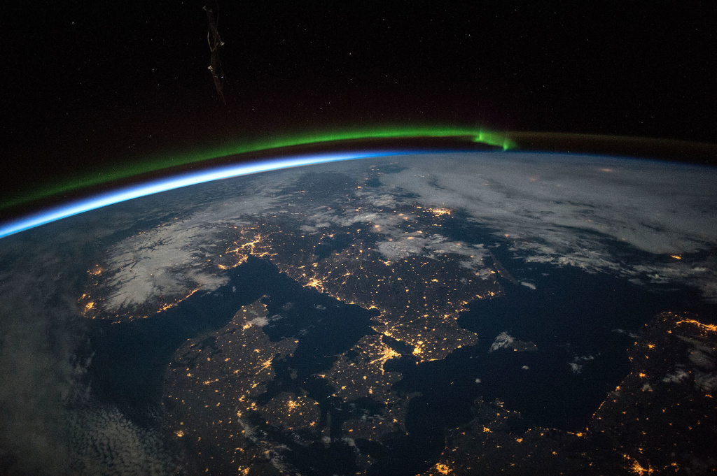 Astronauts aboard the International Space Station took this image of southern Scandinavia lit up at night. A green aurora is visible over the horizon.