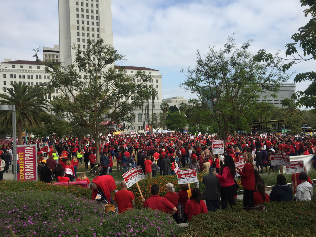 Teachers in bright red shirts holding signs and ringing red bells file into Grand Park on May 24, 2018. UTLA, the union representing LAUSD teachers, says the public rally comes after about a year of working without a contract.