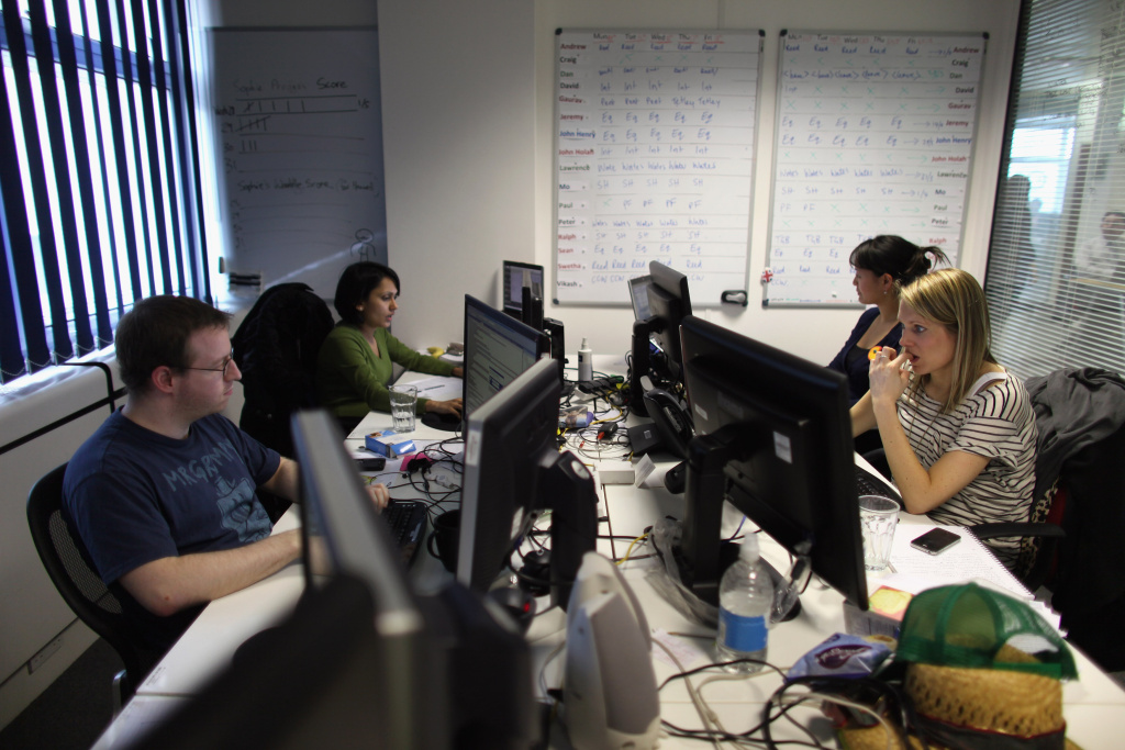 Employees work at computers in the office of 'Content and Code' on the Old Street roundabout in Shoreditch, London, England.