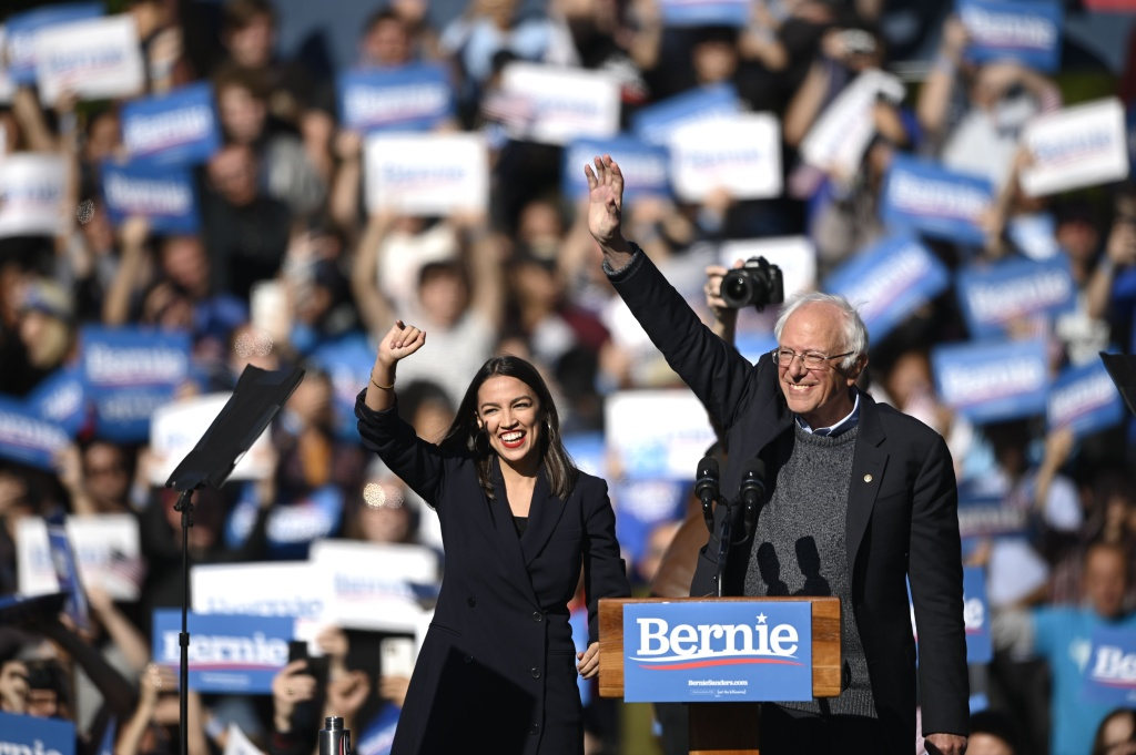 2020 Democratic presidential hopeful US Senator Bernie Sanders (D-VT) and representative Alexandria Ocasio-Cortez (D-NY) wave to a crowd of supporters during a campaign rally.