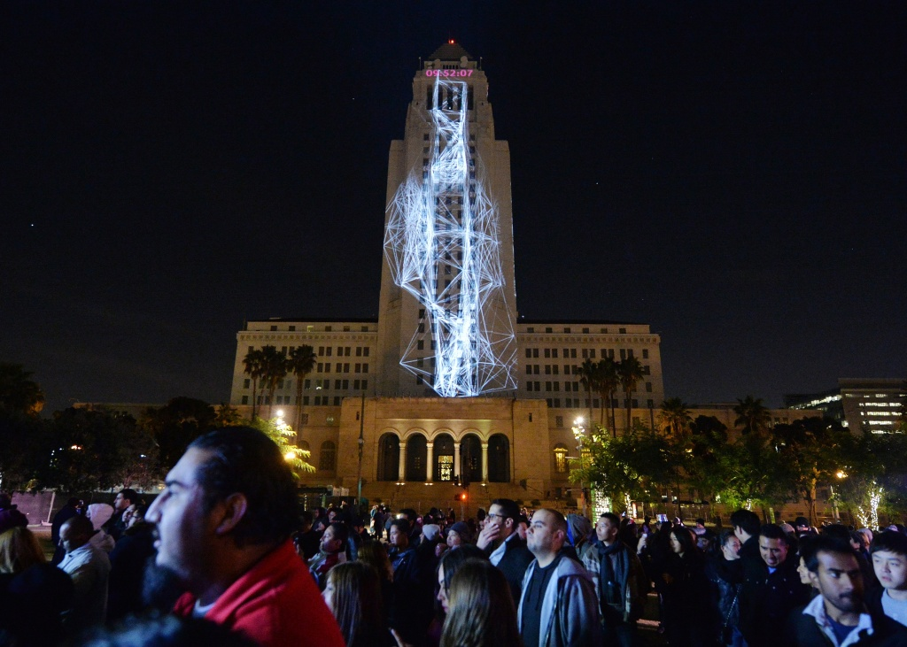 Los Angeles City Hall is lit by projected images while people celebrate at Grand Park's New Yea's Eve event on December 31, 2014.