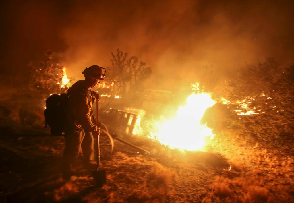 A firefighter watches the Blue Cut wildfire burning near Cajon Pass, north of San Bernardino, California on August 16, 2016.