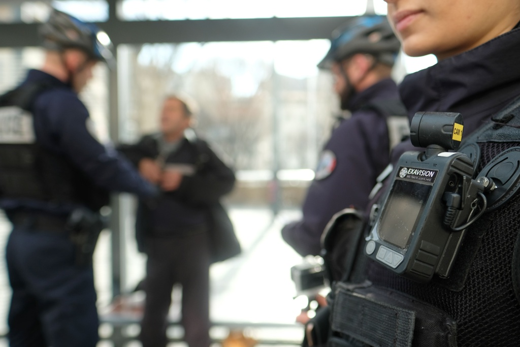 A member of a police patrol conducts a search on a man as one of his colleague stands guard with a body camera attached to the shoulder on February 15, 2017 in Marseille.