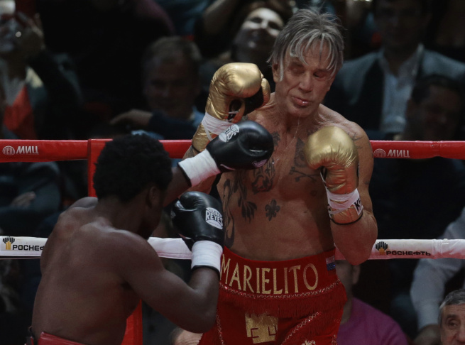 US actor Mickey Rourke, right, holds up his guard against his opponent Elliot Seymour of the United States, during their professional boxing match, at the Luzhniki Stadium, Moscow,Friday, Nov, 28, 2014. Hollywood actor Mickey Rourke returned to the boxing ring Friday at the age of 62, defeating a fighter less than half his age in an exhibition bout.