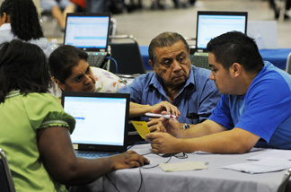 An American family speaks with a bank consultant to restructure their mortgage at the nation's largest loan modification event, which is part of the Neighborhood Assistance Corporation of America's (NACA) 'Save the Dream' tour at the Los Angeles Convention Center, on September 30, 2010. The five-day event, where homeowners can restructure their mortgages to avoid foreclosure, brings together struggling homeowners and major banks.