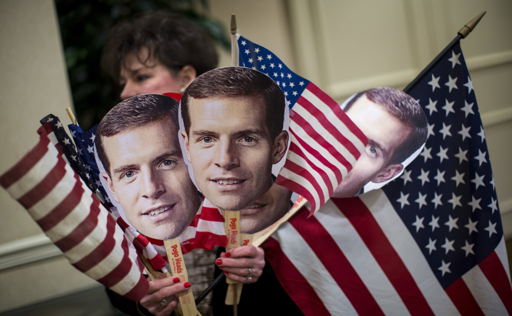 A supporter carries flags and photos of Conor Lamb at an election night event on Tuesday for the Democrat, who has apparently won the congressional seat in Pennsylvania's 18th District.
