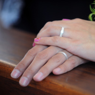 A couples shows their wedding rings during their ceremony.