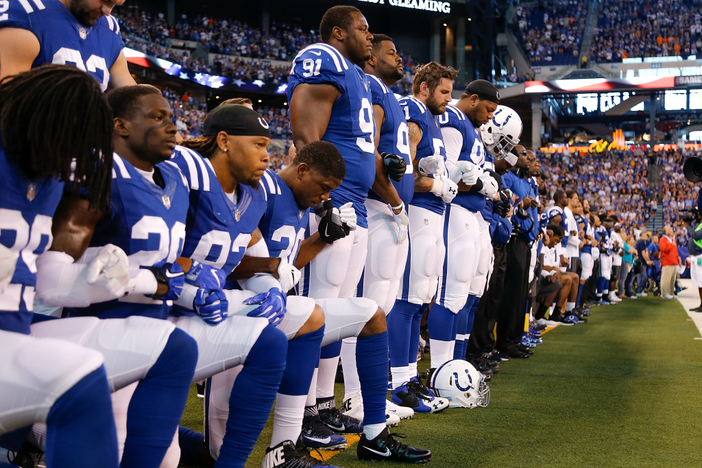 Members of the Indianapolis Colts stand and kneel for the national anthem prior to the start of a game against the Cleveland Browns on September 24, 2017 in Indianapolis, Indiana.