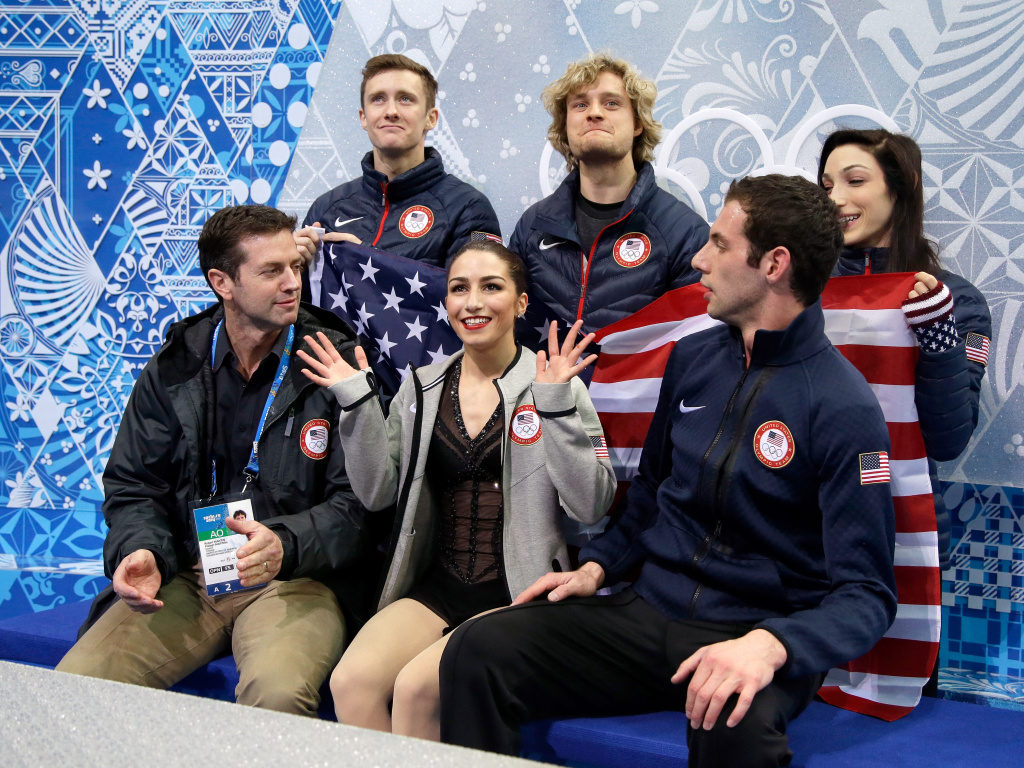 Marissa Castelli (front center) and Simon Shnapir (front right) of the U.S. wait for their scores in the pairs short program Thursday in Sochi. With them are coach Robert Martin and teammates (back, from left) Jeremy Abbott, Charlie White and Meryl Davis.