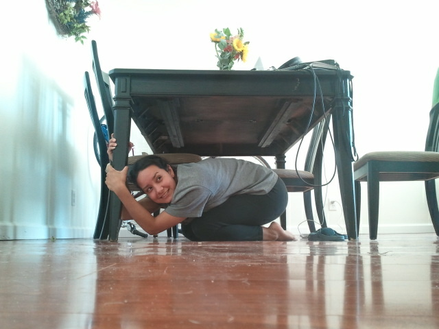 KPCC's Erika Aguilar finds cover under a dining room table at her home practicing the Shakeout earthquake drill,