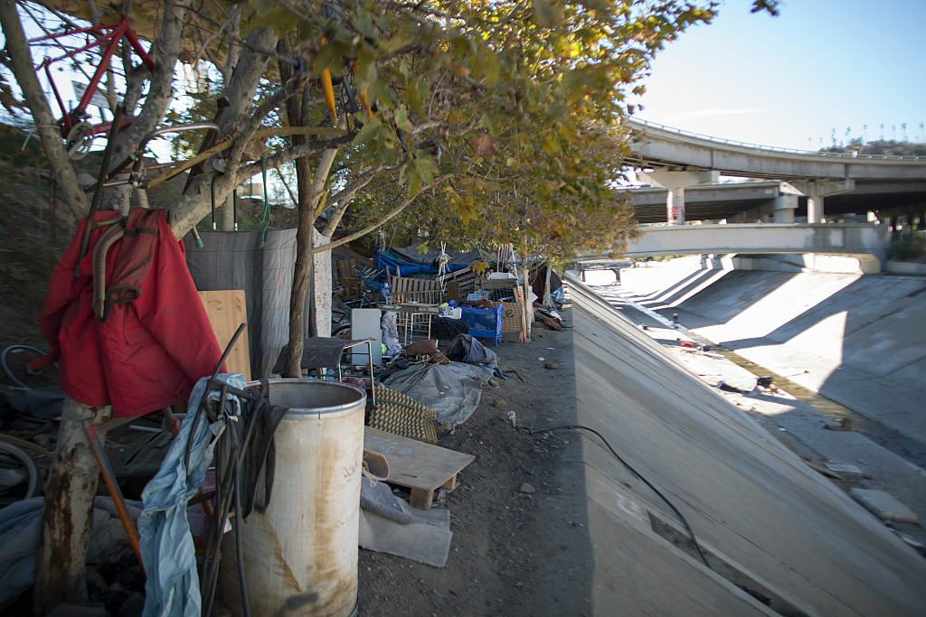 Homeless encampments line the banks above the concreted channel of the Arroyo Seco Creek on in Los Angeles, California.